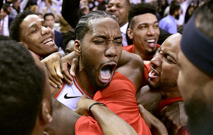 Toronto Raptors forward Kawhi Leonard, center, celebrates his game-winning basket as time expired at the end of an NBA Eastern Conference semifinal game against the Philadelphia 76ers, in Toronto on Sunday, May 12, 2019. Toronto won 92-90. (Frank Gunn/The Canadian Press via AP)