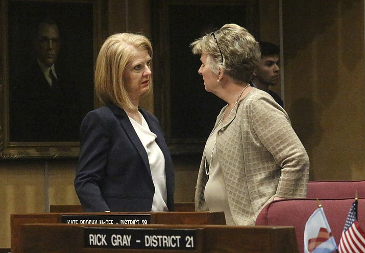 In this April 1, 2019 photo, Arizona Sen. Heather Carter, left, chats with Sen. Kate Brophy McGee during a break in the Arizona Senate in Phoenix. Carter and fellow Republican, Rep. John Allen, are facing off over competing proposals to regulate tobacco and vaping products. (Bob Christie/AP)