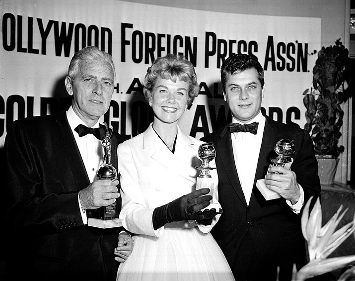 In this Feb. 26, 1958 file photo, actress Doris Day, center, Tony Curtis, right, and Buddy Adler pose with their awards presented to them by the Hollywood Foreign Press Association at its annual awards dinner in the Cocoanut Grove in Los Angeles. Day, whose wholesome screen presence stood for a time of innocence in '60s films, has died, her foundation says. She was 97. The Doris Day Animal Foundation confirmed Day died early Monday, May 13, 2019, at her Carmel Valley, California, home. (AP Photo, File)