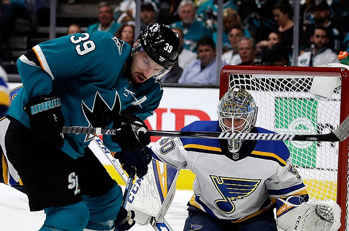 San Jose's Logan Couture, left, moves the puck against St. Louis goalie Jordan Binnington (50) during the first period in Game 2 of the NHL  Stanley Cup Western Conference finals Monday, May 13, 2019, in San Jose, Calif. (Ben Margot/AP)