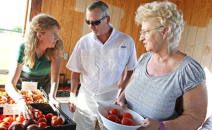 "Hope Barnett of Willowbrook Farms answers questions at the Verde Valley Farmers' Market. This year, Willowbrook hopes to have chard, kale, lettuce mix, head lettuce, radishes, garlic scapes, pea shoots and sunflower sprouts, and ""lots of yummy greens."" VVN/Bill Helm"