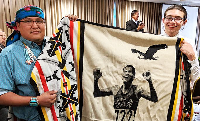 Native youth Dreamstarters Carl Petersen, Cheyenne River Sioux and Kevin Belin, Navajo hold up a prized Pendleton blanket honoring Billy Mills. Mills was speaking in the background and thanking the crowd for honoring Native youth. (Photo/Vincent Schilling)
