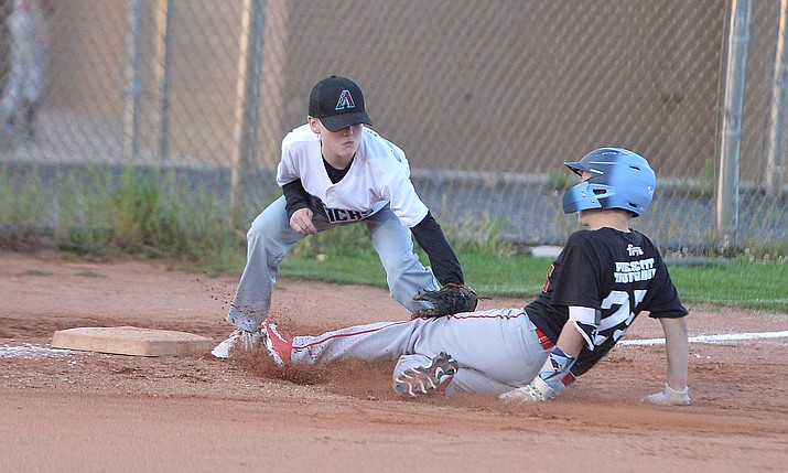 Carter Cashatt tags Adrin Sanderford out at third during the Prescott Little League majors City Championship semi-final game Tuesday, May 14.  (Les Stukenberg/Courier)