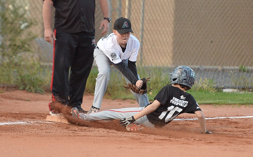 Mike Falick slides safely into third under the tag of Carter Cashatt during the Prescott Little League majors City Championship semi-final game Tuesday, May 14.  (Les Stukenberg/Courier)