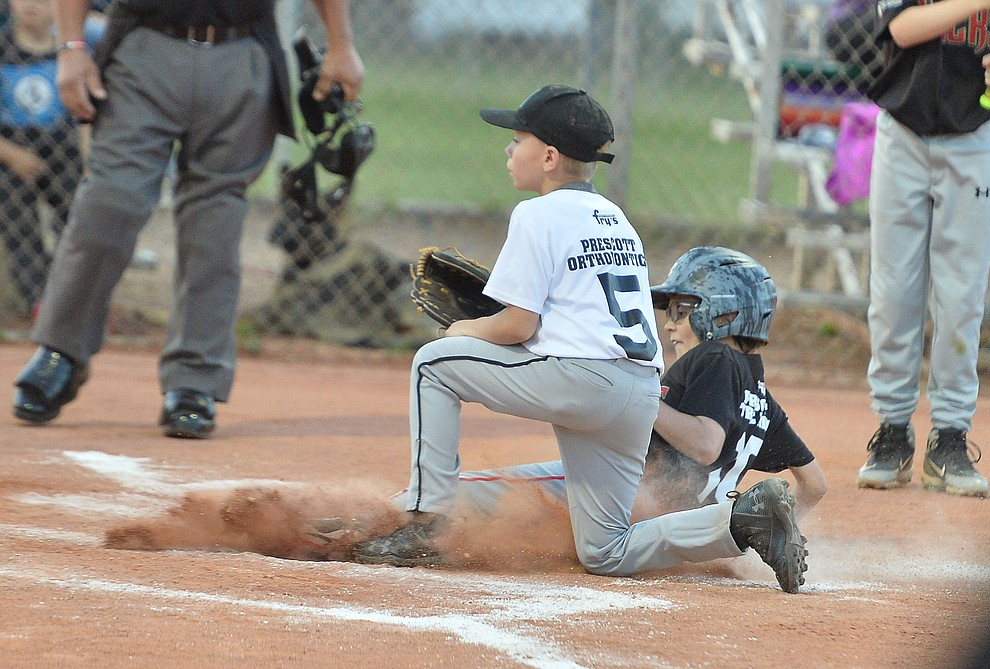 Mike Falick slides safely home under Trace Overton during the Prescott Little League majors City Championship semi-final game Tuesday, May 14.  (Les Stukenberg/Courier)