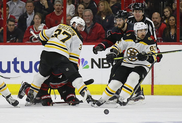Boston Bruins' Patrice Bergeron (37) and Brad Marchand (63) skate for the puck with Carolina Hurricanes' Brett Pesce (22) and Jordan Staal during the second period in Game 3 of the NHL Stanley Cup Eastern Conference final series in Raleigh, N.C., Tuesday, May 14, 2019. (Gerry Broome/AP)