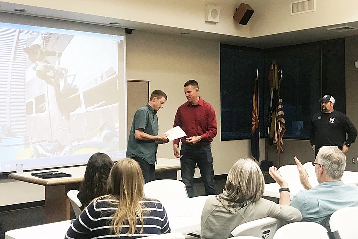 Williams Volunteer Firefighter Ryan Thibault (left) is awarded a certificate of completion for a Firefighter I and II course from Coconino Community College May 11. (Loretta Yerian/WGCN)