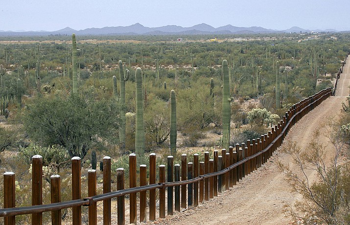 This Feb. 17, 2006 file photo shows the international border line made up of bollards: irregular, concrete-filled steel poles, seperating Mexico, left from the United States, in the Organ Pipe National Monument near Lukeville, Ariz. The federal government plans on replacing barriers through 100 miles of the southern border in California and Arizona, including through a this national monument and a wildlife refuge, according to government documents and environmental advocates. The Department of Homeland Security on Tuesday waived environmental and dozens of other laws to build more barriers along the southern border. (Matt York/AP, File)