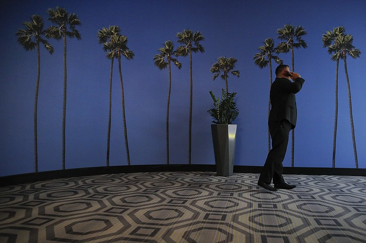 In this May 4, 2018, file photo a man talks on the phone in a hallway adorned with the palm tree-printed wallpaper at a hotel near the Los Angeles International Airport in Los Angeles. U.S. regulators are proposing new measures intended to thwart billions of annoying robocalls received by Americans each year. The rising volume of unwanted calls in the last few years has created pressure on Congress, regulators and phone companies to do something to act. (Jae C. Hong/AP, File)