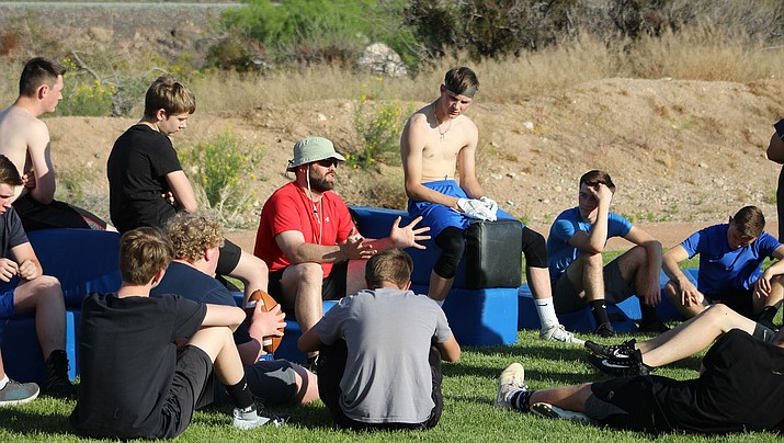 Kingman Academy football coach John Morgando speaks with the Tigers during spring practice Tuesday at Southside Park. (Photo by Beau Bearden/Daily Miner)