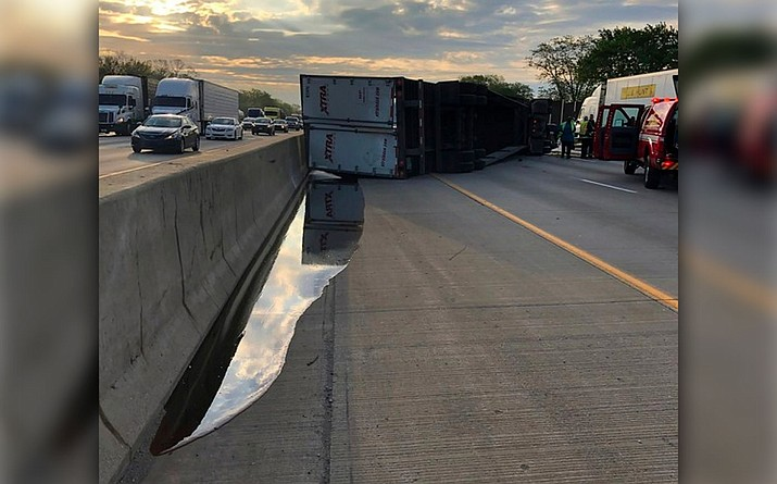 A semi-trailer hauling honey overturned on a northwestern Indiana highway, spilling the sticky substance and restricting travel for hours in Hammond, Ind., Wednesday, May 15, 2019. State police say the truck was hauling about 41,000 pounds of amber honey along Interstate 80/94 when the driver lost control and the truck overturned. At least four containers of honey were leaking and mixing with diesel fuel from the overturned vehicle. (Indiana State Police via AP)