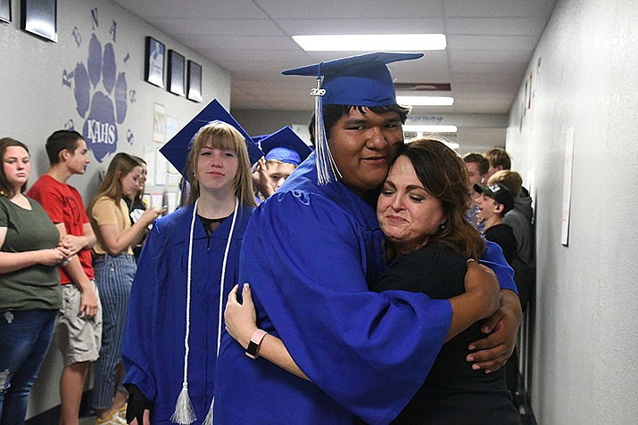 Kingman Academy of Learning High School teacher, Jen Perea, hugs a graduating student as they walk through the halls among their peers. (Photo by Vanessa Espinoza/Daily Miner)