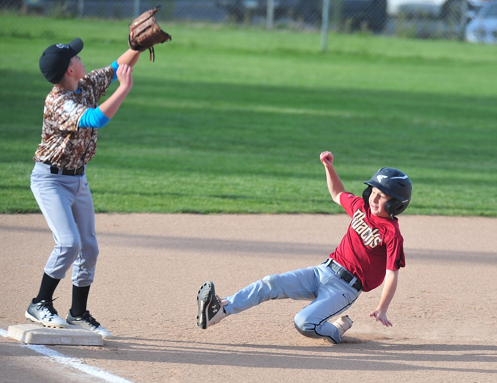 Nick Poynor slides into third as Pace Norman waits on the throw as the Grand Highland Cobras faced off against the Process Driven Baseball Diamondbacks in the Prescott Little League Minors City Championship Game Friday, May 17.  (Les Stukenberg/Courier)