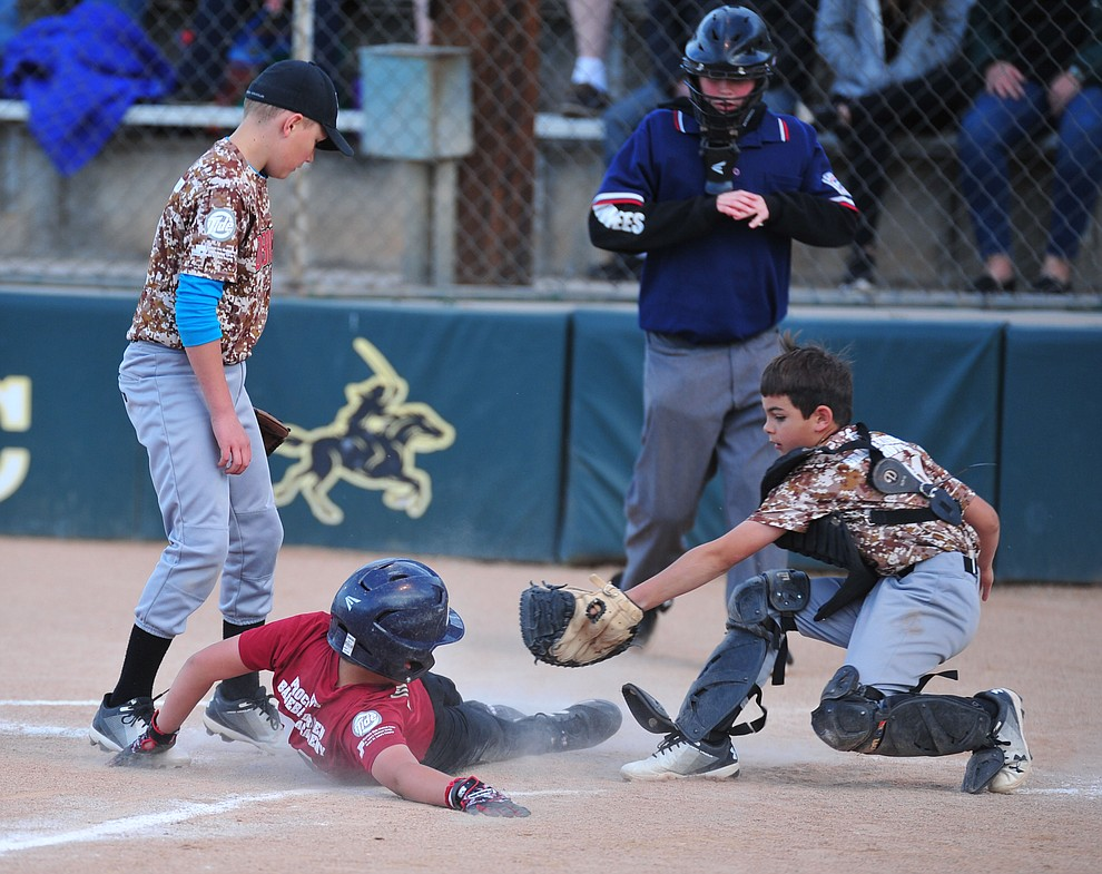Quinton Del Prata scores the game winning run between  Pace Norman and Jason Placencia as the Grand Highland Cobras faced off against the Process Driven Baseball Diamondbacks in the Prescott Little League Minors City Championship Game Friday, May 17.  (Les Stukenberg/Courier)