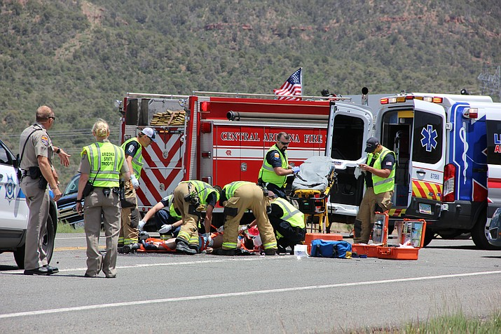 Emergency responders treat a seriously-injured man on Highway 89A after his motorcycle crashed into a sedan near Mingus Mountain midday Friday, May 17. (Max Efrein/Daily Courier)