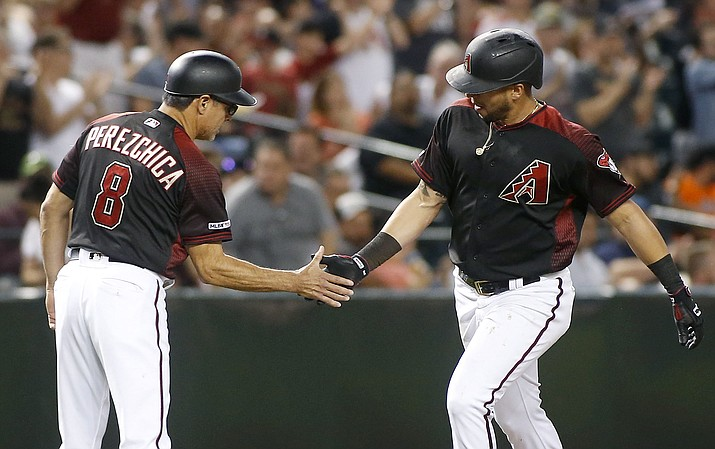 Arizona Diamondbacks' David Peralta, right, is congratulated by third base coach Tony Perezchica after hitting a solo home run against the San Francisco Giants during the fourth inning of a baseball game, Friday, May 17, 2019, in Phoenix. (Ralph Freso/AP)