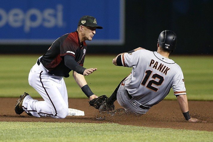 Arizona Diamondbacks shortstop Nick Ahmed, left, tags out San Francisco Giants' Joe Panik on a steal attempt during the fourth inning of a baseball game Saturday, May 18, 2019, in Phoenix. (Ralph Freso/AP)