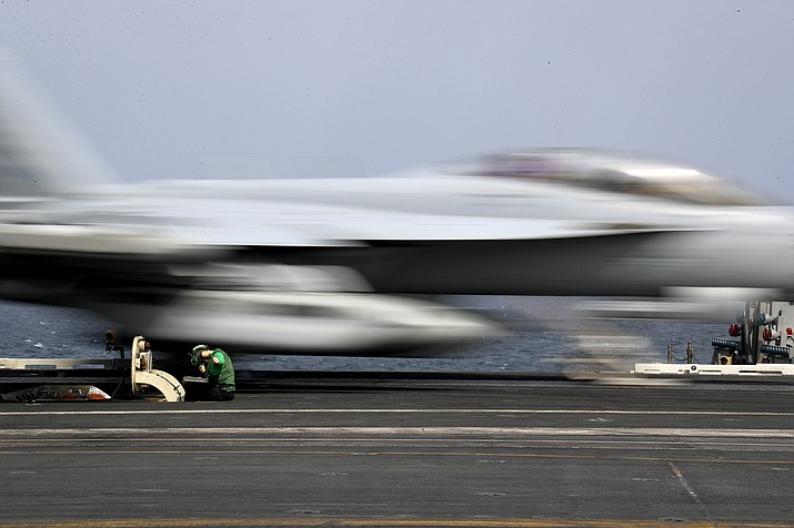 """Aviation Boatswain's Mate Airman Kayla Pettit operates a center deck station Thursday, May 16, 2019, as an F-18 Super Hornet takes off from the USS Abraham Lincoln aircraft carrier in the Arabian Sea. On Saturday, May 18, 2019, U.S. diplomats warned that commercial airliners flying over the wider Persian Gulf faced a risk of being """"misidentified"""" amid heightened tensions between the U.S. and Iran. (Mass Communication Specialist 3rd Class Jeff Sherman, U.S. Navy via AP)"""