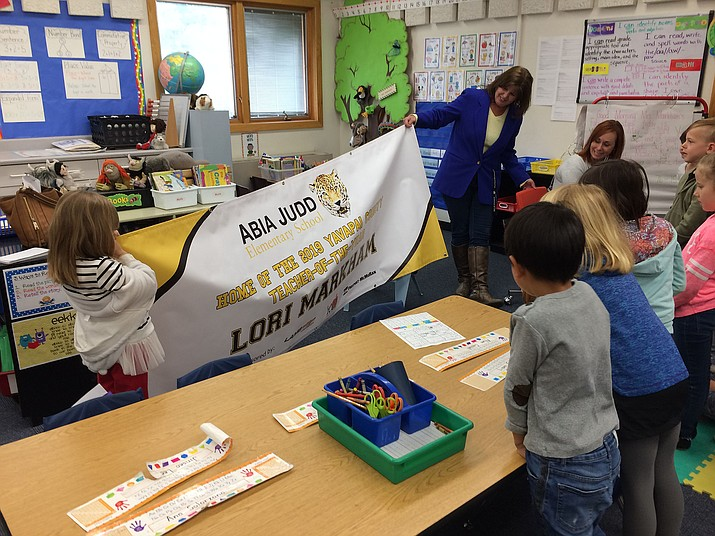 Abia Judd Elementary Principal Stephanie Hillig shows the 2019 Yavapai County Teacher of the Year banner to winner Lori Markham's first-grade class. The banner from the Yavapai County Education Foundation now hangs right behind the front doors of the school. (Nanci Hutson/Courier)
