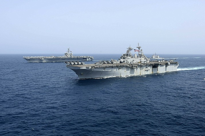 "In this Friday, May 17, 2019, photo released by the U.S. Navy, the amphibious assault ship USS Kearsarge sails in front of the USS Abraham Lincoln aircraft carrier in the Arabian Sea. Commercial airliners flying over the Persian Gulf risk being targeted by ""miscalculation or misidentification"" from the Iranian military amid heightened tensions between the Islamic Republic and the U.S., American diplomats warned Saturday, May 18, 2019, even as both Washington and Tehran say they don't seek war. (Mass Communication Specialist 1st Class Brian M. Wilbur, U.S. Navy)"