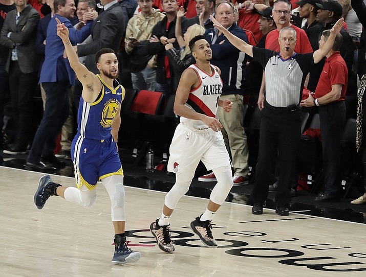 Golden State guard Stephen Curry, left, celebrates as he runs next to Portland guard CJ McCollum, center, at the end of Game 4 of the NBA playoffs Western Conference finals, Monday, May 20, 2019, in Portland, Ore. (Ted S. Warren/AP)