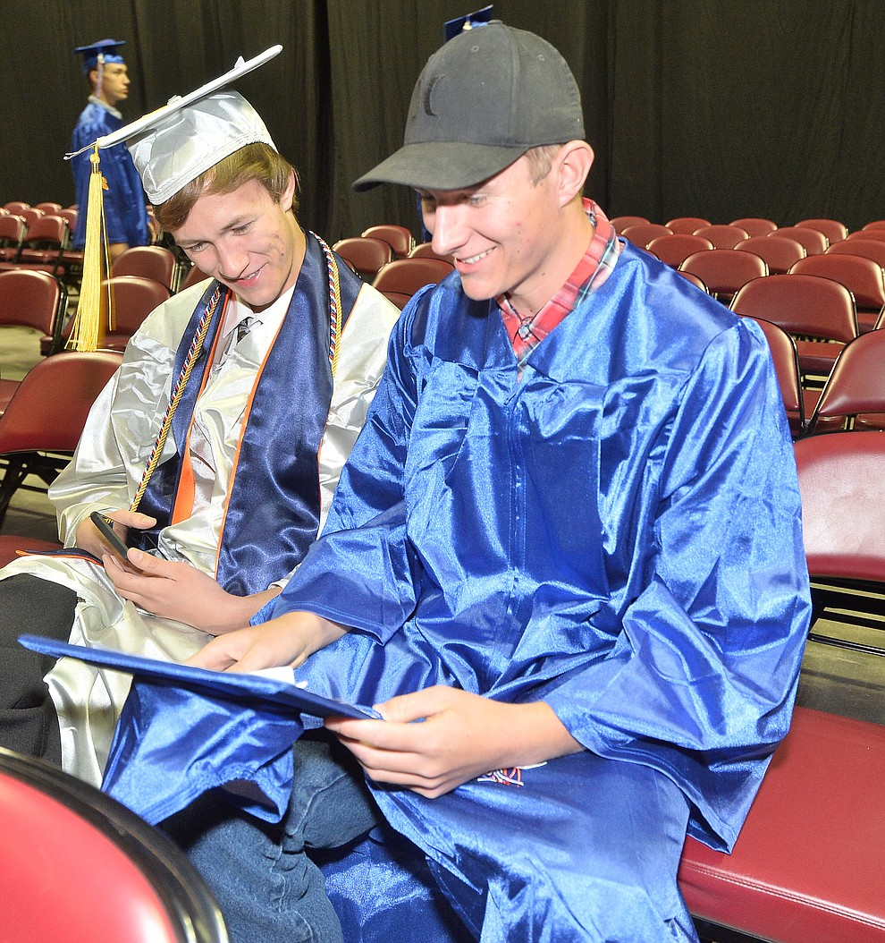 Nicholas Swartwout and Brandon Farnsworth check out the top of his mortar board before Chino Valley HIgh School graduated 153 students in a commencement ceremony Wednesday, May 22 at the Findlay Toyota Center in Prescott Valley.  (Les Stukenberg/Courier)