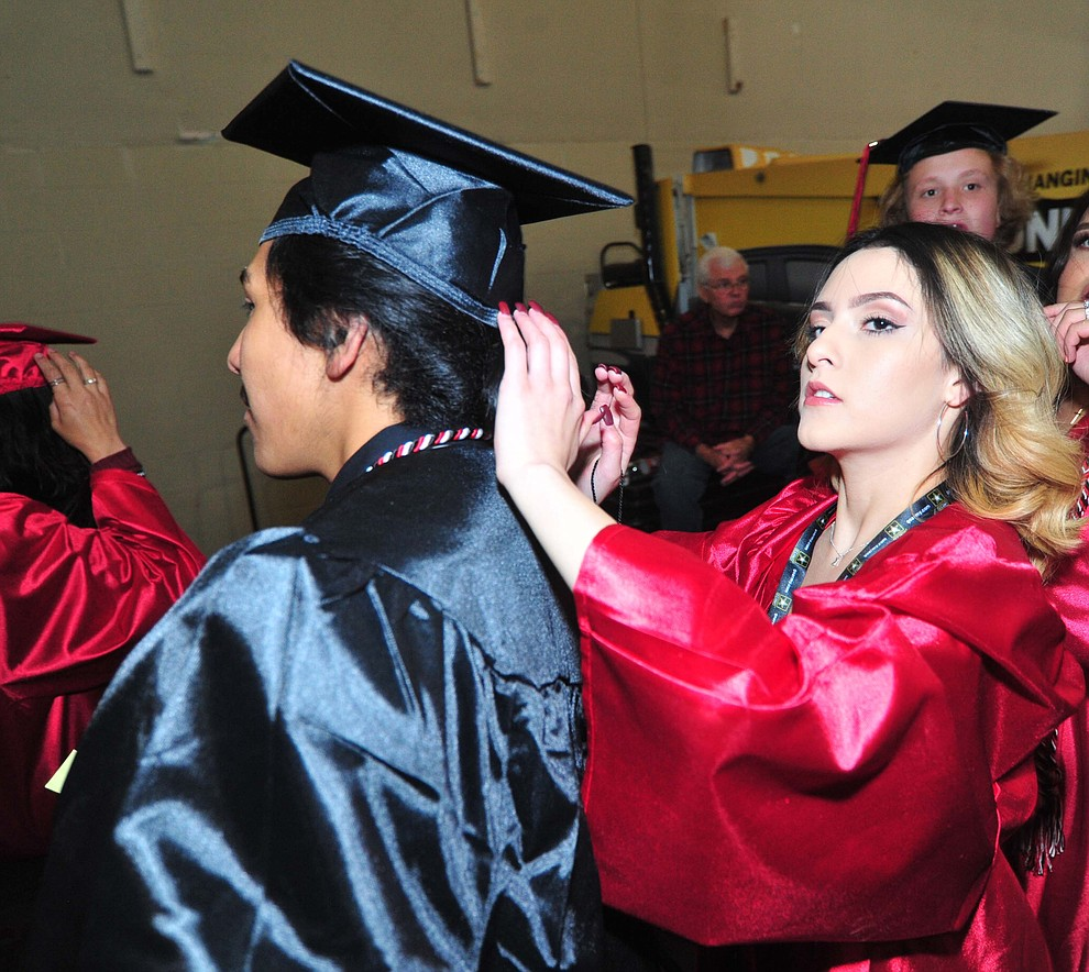 Karina Ayala Flores helps Jose Gutierrez before Bradshaw Mountain High School graduated 334 students in a commencement ceremony Thursday, May 23 at the Findlay Toyota Center in Prescott Valley. (Les Stukenberg/Courier)