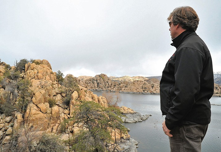 Chris Hosking, the City of Prescott's trails specialist, looks out over a piece of land at Watson Lake that will complete a trail circling the whole lake Wednesday. (Matt Hinshaw/The Daily Courier)