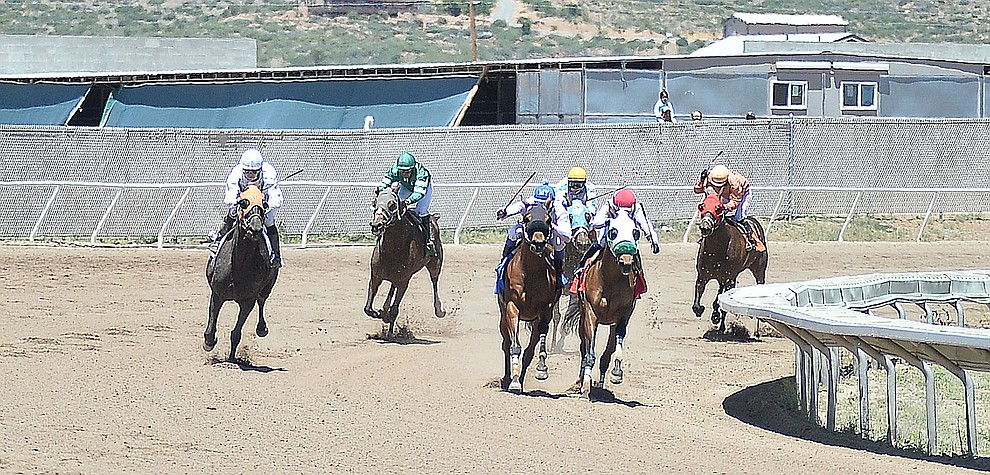 Horses round the far turn in the first race at opening day of Arizona Downs Friday, May 24 in Prescott Valley. The racetrack reopens under new ownership after being closed for 10 years. (Les Stukenberg/Courier)