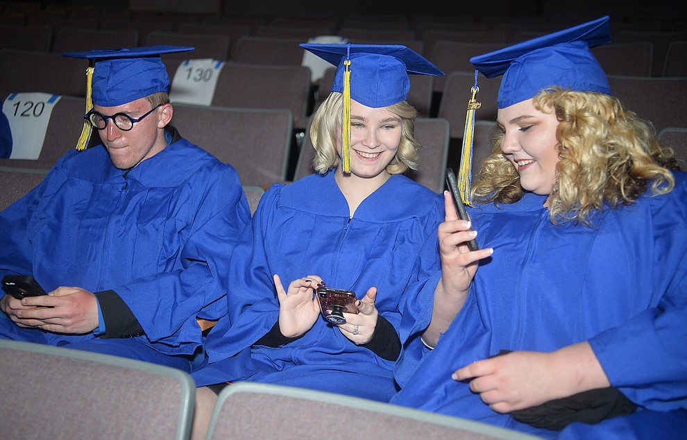 Alec Peterson, Stephanie Pasant and Cheyenne Williams check their phones before Prescott High School graduated 301 students in a commencement ceremony Friday, May 24 on Bill Shepard Field in Prescott. (Les Stukenberg/Courier)