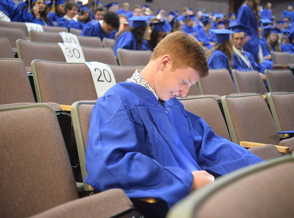 William Ramsay gets a laugh from his phone before Prescott High School graduated 301 students in a commencement ceremony Friday, May 24 on Bill Shepard Field in Prescott. (Les Stukenberg/Courier)