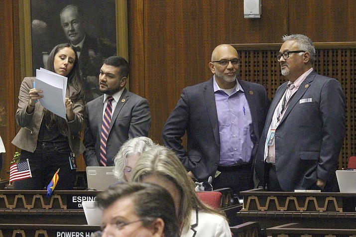 Four Democratic members of the Arizona House, from left, Athena Salman, Andres Cano, Diego Espinoza and Lorenzo Sierra confer on the House floor as a state budget plan awaits action, Thursday, May 23, 2019 in Phoenix. (Bob Christie/AP)