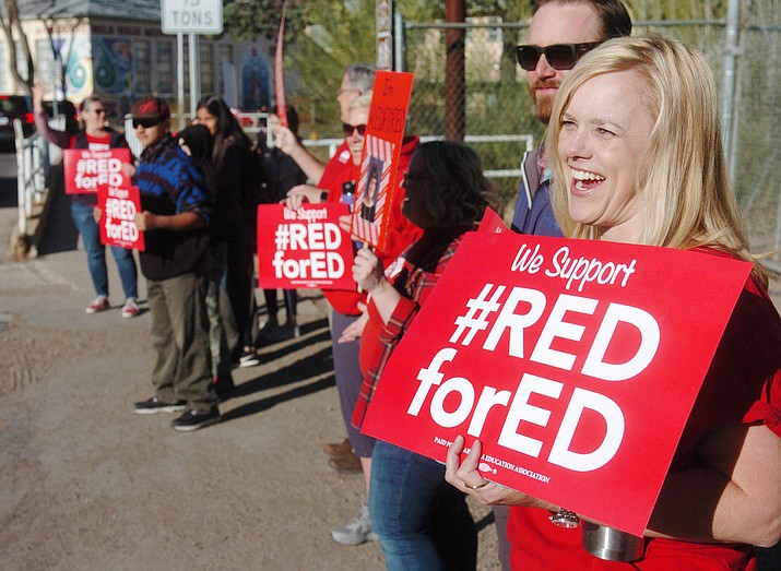Seventh-grade science teacher Alyson Anderson and other Prescott Mile High Middle School teachers and students welcome parents as they drop students off as part of the #RedForEd movement, Wednesday, April 18, 2018. The movement was successful in getting lawmakers to make teachers' salaries a priority. In 2020, a potential ballot measure is seeking a tax on higher incomes to help fund education. (Les Stukenberg/Courier, file)