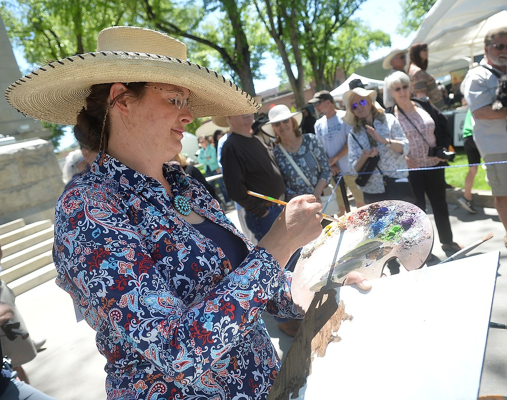 Sarah Phippen paints during the quick draw contest at the Phippen Western Art Show & Sale Saturday, May 25. in on the Courthouse Plaza in Prescott. (Les Stukenberg/Courier)