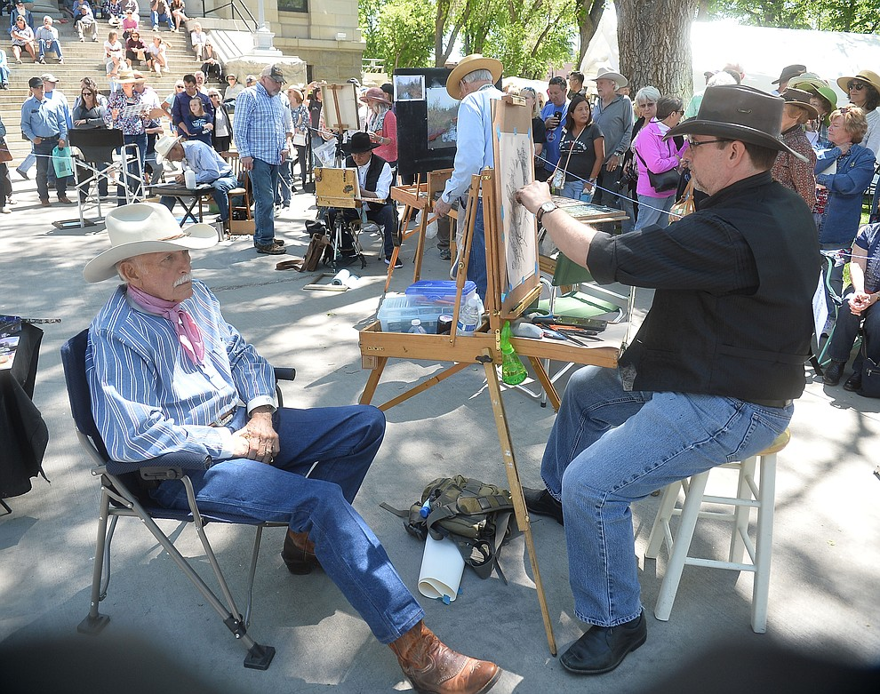 Steve Atkinson uses a model to paint during the quick draw contest at the Phippen Western Art Show & Sale Saturday, May 25. in on the Courthouse Plaza in Prescott. (Les Stukenberg/Courier)