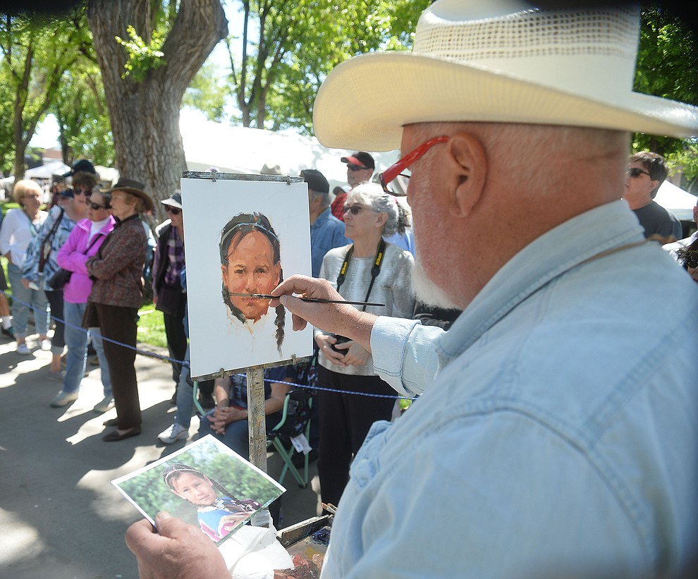 Sam Thiewes paints from a photograph during the quick draw contest at the Phippen Western Art Show & Sale Saturday, May 25. in on the Courthouse Plaza in Prescott. (Les Stukenberg/Courier)