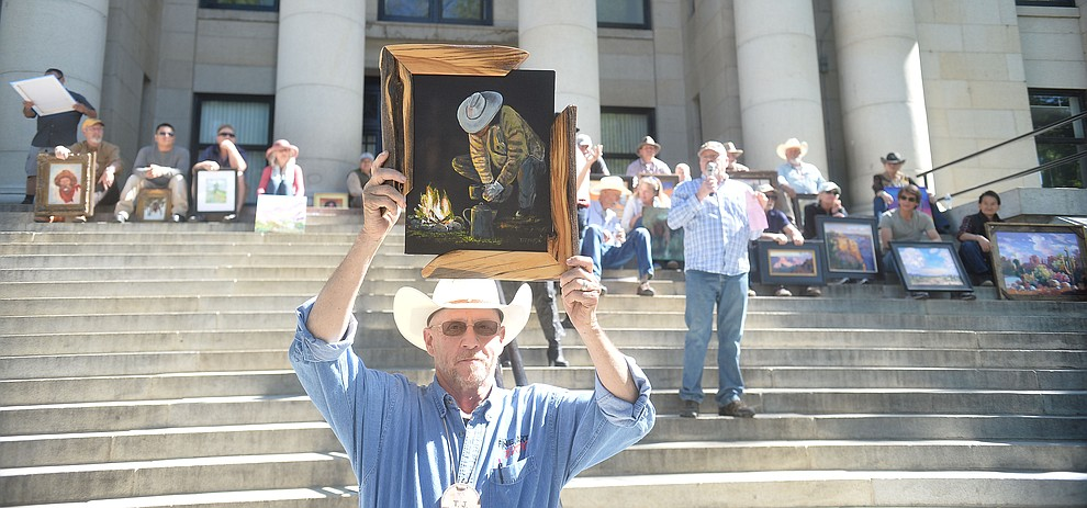 T.J. Thompson shows off his work completed in the quick draw contest as auctioneer Jacy Lee works the crowd at the Phippen Western Art Show & Sale Saturday, May 25. in on the Courthouse Plaza in Prescott. (Les Stukenberg/Courier)