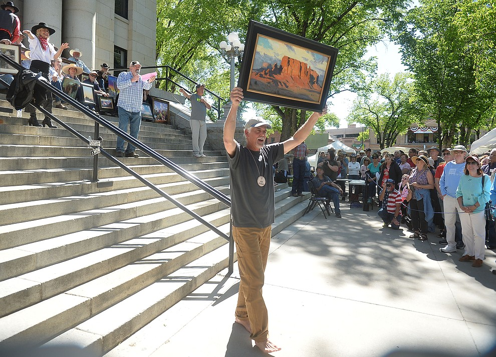 Bill Cramer shows off his work during an auction following the quick draw contest at the Phippen Western Art Show & Sale Saturday, May 25. in on the Courthouse Plaza in Prescott. (Les Stukenberg/Courier)