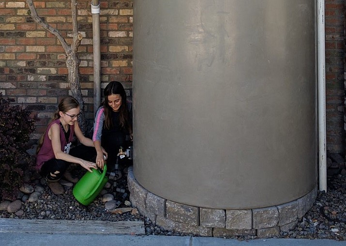 Outdoors Explorer Club members Adessa Kunszmann, left, and Ariella Centeno, right, use the 1,000-gallon rain barrel at the Prescott Public Library to get water for the library's educational garden plot. (City of Prescott/Courtesy)