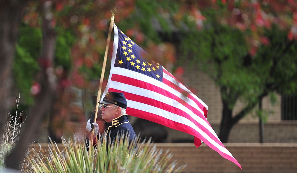A participant walks with a flag replicated from the late 1800's to the Memorial Day Ceremony at the Citizens Cemetery Monday, May 27 in Prescott. (Les Stukenberg/Courier)