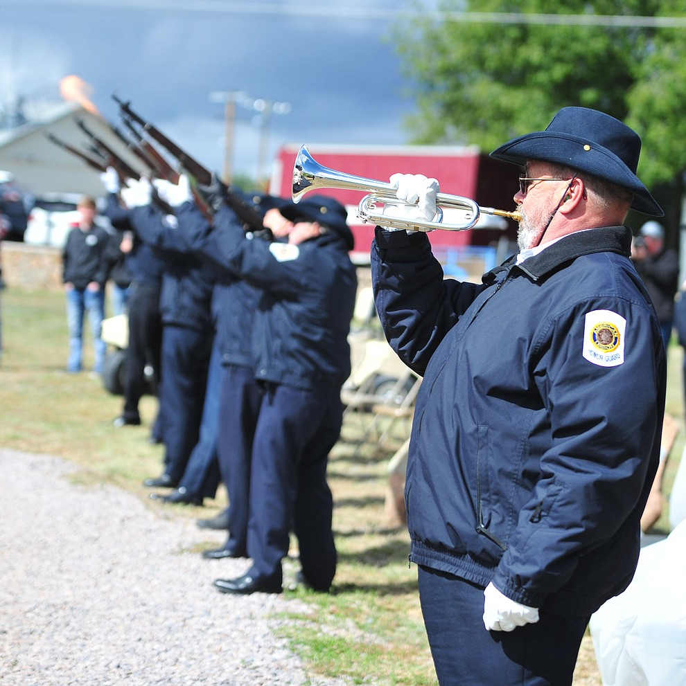 "Bradley S Moore plays ""To the Colors"" as the American Legion Post 6 Honor Guard fires a rifle volley during the Memorial Day Ceremony at the Citizens Cemetery Monday, May 27 in Prescott. (Les Stukenberg/Courier)"
