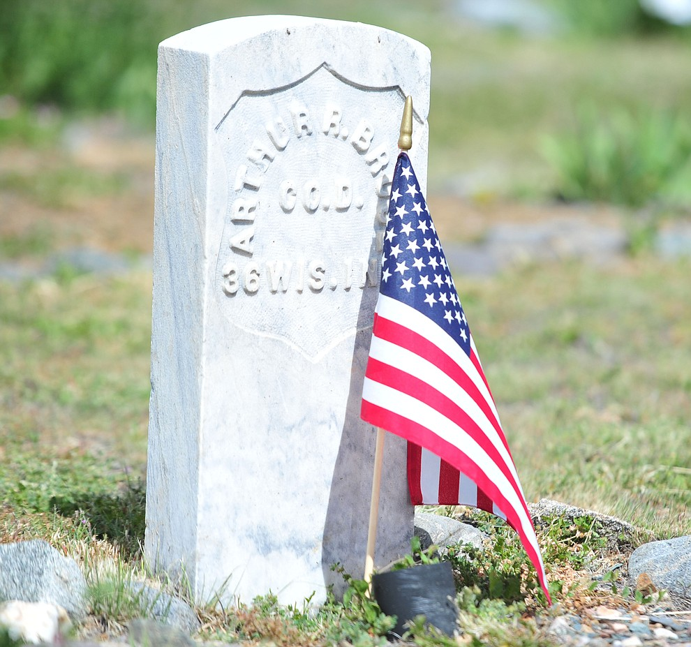 A grave of where a soldier buried is honored with a flag during the Memorial Day Ceremony at the Citizens Cemetery Monday, May 27 in Prescott. (Les Stukenberg/Courier)