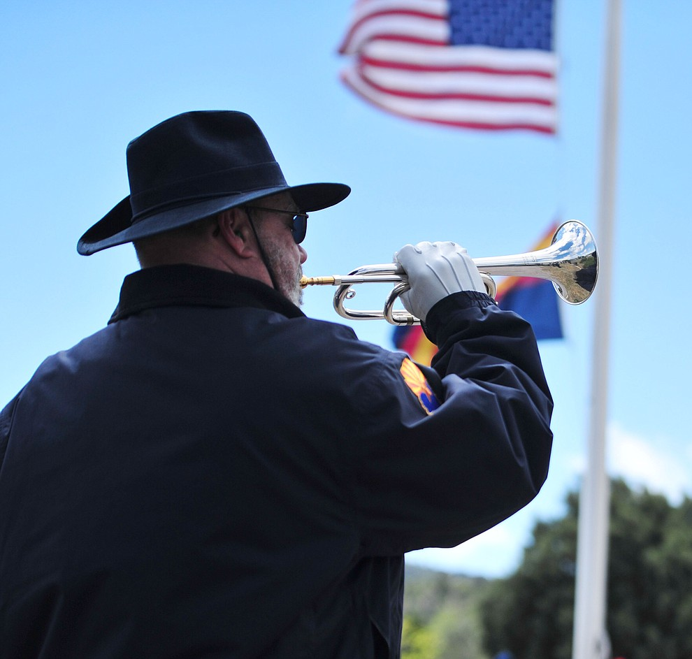 "Bradley S Moore plays ""Taps"" as the American Legion Post 6 Honor Guard fires a rifle volley during the Memorial Day Ceremony at the Citizens Cemetery Monday, May 27 in Prescott. (Les Stukenberg/Courier)"