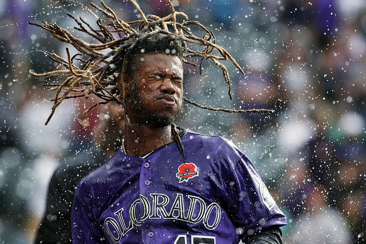 Colorado Rockies' Raimel Tapia shakes his head after being doused in celebration of his walk-off single off Arizona Diamondbacks relief pitcher Matt Andriese in the 11th inning of a baseball game, Monday, May 27, 2019, in Denver. The Rockies won 4-3. (David Zalubowski/AP)