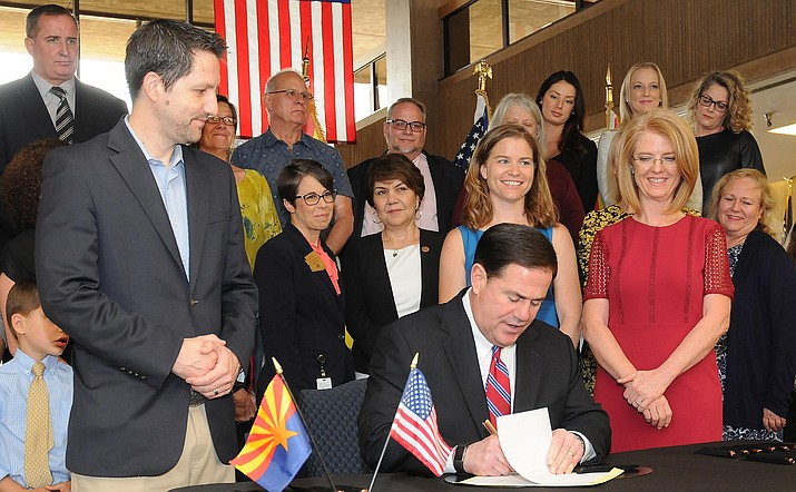 Gov. Doug Ducey performs ceremonial signing Tuesday of bill to give victims of sex abuse more time to sue. With him are Sen. Paul Boyer, former speed skater Bridie Farrell, and Sen. Heather Carter. (Capitol Media Services photo by Howard Fischer)