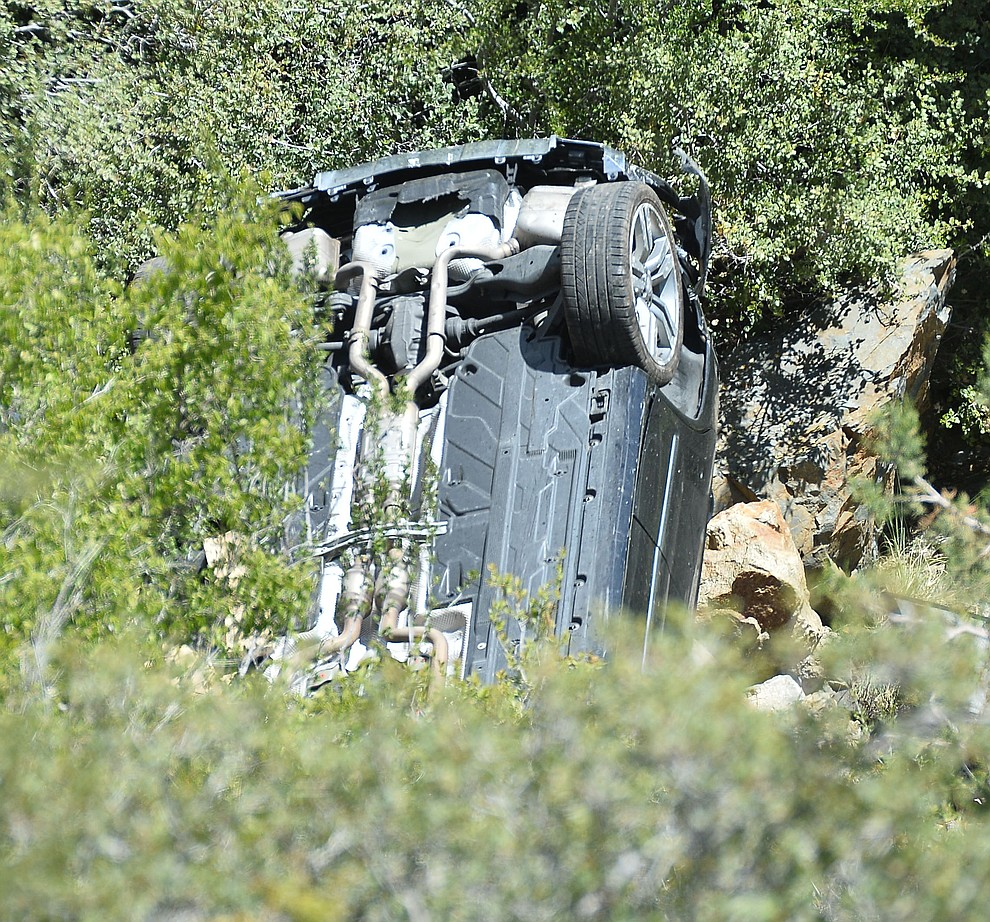 Arizona Department of Public Safety (DPS) investigators are on the scene where a stolen vehicle was run off a cliff at mile marker 303 on Highway 89 Monday, May 28 between Prescott and Wilhoit. The vehicle is approximately 500 feet down a steep hillside, landing in a drainage. (Les Stukenberg/Courier)