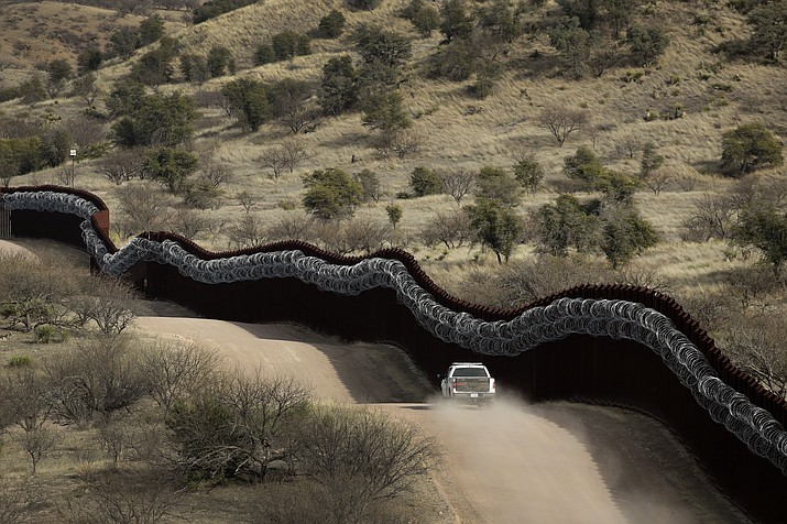 This March 2, 2019, file photo, shows a Customs and Border Control agent patrolling on the US side of a razor-wire-covered border wall along the Mexico east of Nogales, Ariz. A border activist charged with helping a pair of migrants with water, food and lodging is set to go on trial in U.S. court in Arizona. Defendant Scott Daniel Warren has argued that his spiritual values compel him to help all people in distress. The trial is scheduled to begin Wednesday, May 29, 2019, in Tucson, with the 36-year-old Warren charged with harboring migrants and conspiring to transport and harbor two Mexican men found with him who were in the U.S. illegally. (Charlie Riedel/AP, file)