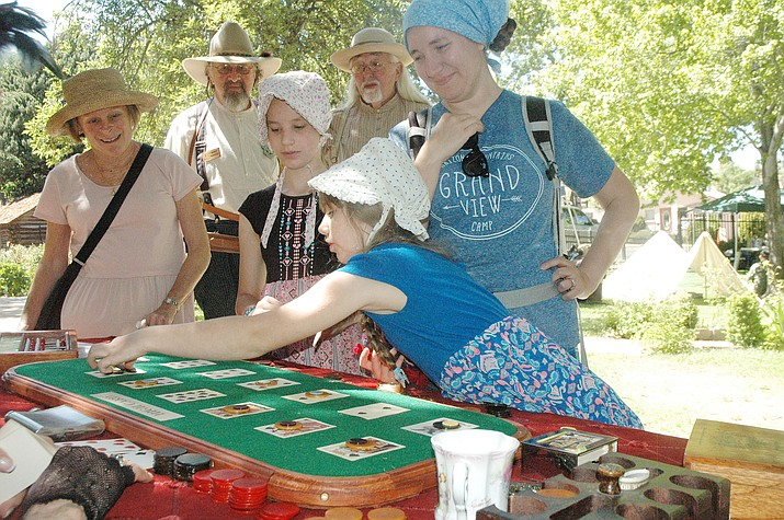 Wearing bonnets, Delilia, center, and Aurellia Klein play a game of Faro while their mother, Liana Klein, right, and others look on at the Sharlot Hall Museum's 46th annual Folk Arts Fair on Saturday, June. 1. (Jason Wheeler/Courier)