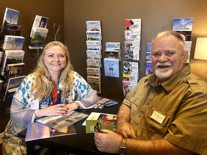 Owners Belinda Sunderland and Stan Kephart sit in the travel-library area of the new agency that they opened May 1 on White Spar Road in Prescott. With years of travel-counseling experience, the two say their business would focus on creating personalized travel experiences. (Cindy Barks/Courier)