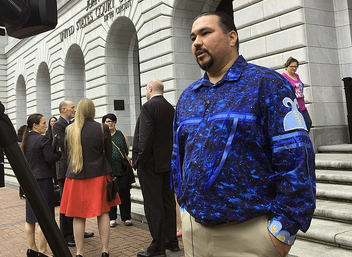 Tehassi Hill, tribal chairman of the Oneida Nation, stands outside a federal appeals court Wednesday, March 13, 2019, in New Orleans, following arguments on the constitutionality of a law giving Native American families preference in adoption of Native American children. (Kevin McGill/AP, file)